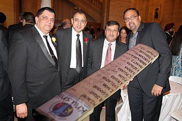 Rajeev Bambari, Atul Kumria, Prabhu Dayal and Kapil Kumria pose with the signed cricket bat.
