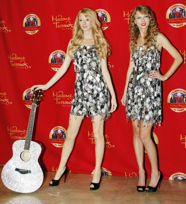 Taylor Swift (right) poses with her wax likeness during an unveiling of the statue at Madame Tussauds in New York