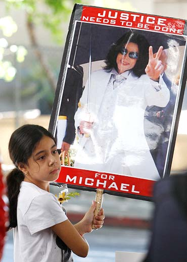 A young fan of late Michael Jackson holds a sign outside a court hearing in Los Angeles