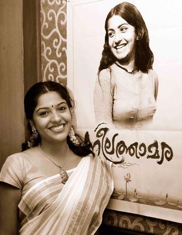 Archana Kavi posing in front of Neelathamara's poster
