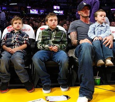 David Beckham watches an NBA basketball game with his sons (left to right) Romeo, Brooklyn and Cruz