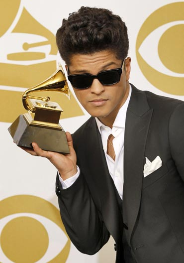 Bruno Mars poses backstage with his award for Best Male Pop Vocal Performance for Just The Way You Are