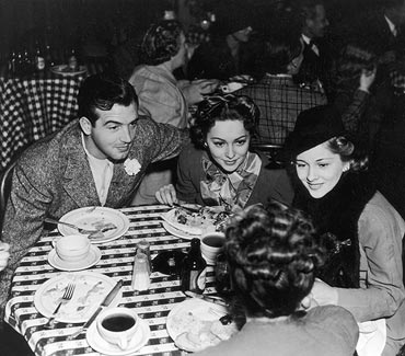 Circa 1940: Olivia de Havilland with her sister Joan Fontaine and actor John Payne