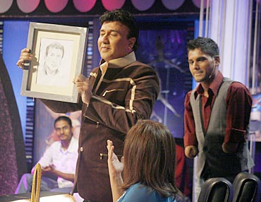 Judge Anu Malik shows one of Dhaval's paintings