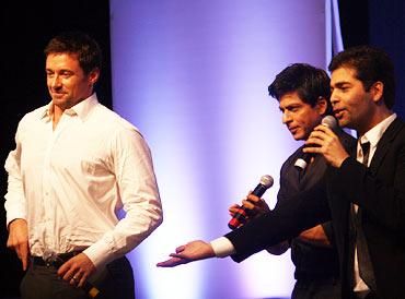 Hugh Jackman seems to adjusts his trousers as Shah Rukh Khan and Karan Johar show him dance moves