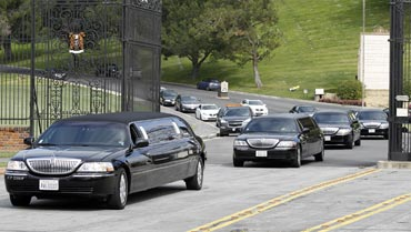 Limousines carrying Liz Taylor's relatives leave after her funeral at Forest Lawn Memorial Park in California
