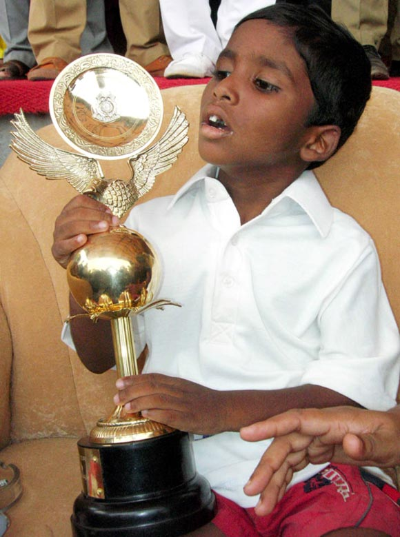 Budhia Singh, a four-year-old child, holds his trophy after a marathon in the eastern Indian city of Bhubaneswar