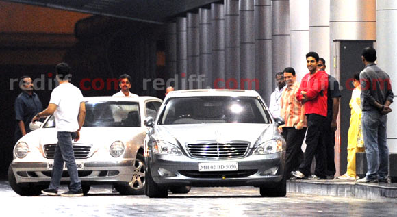 Abhishek Bachchan grins next to the cars the family arrived in