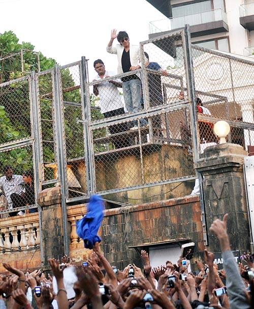 Shah Rukh Khan waves to the crowd gathered in front of his house