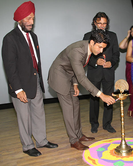 Farhan Akhtar lights a lamp as Milkha Singh, Rakeysh Omprakash Mehra look on