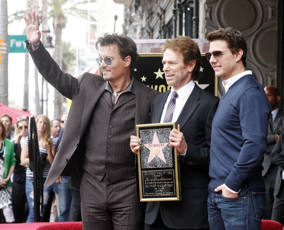 Johnny Depp and Tom Cruise pose with film and television producer Jerry Bruckheimer
