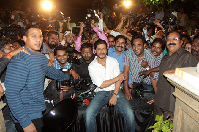 Shah Rukh Khan poses with the media