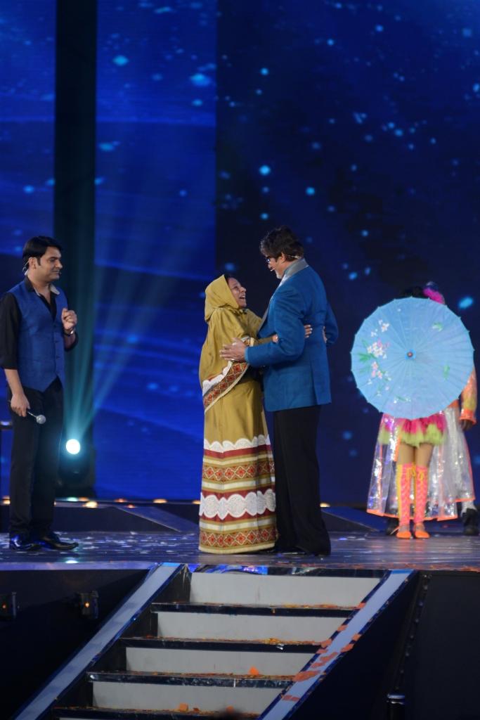 Amitabh Bachchan hugs a fan at the premiere of Kaun Banega Crorepati while Kapil Sharma looks on