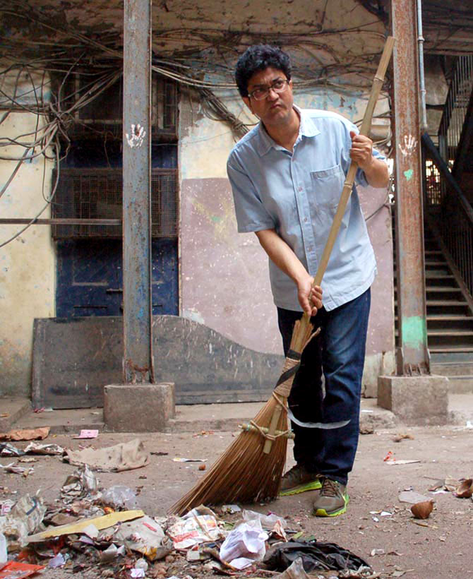 Prasoon Joshi cleans the streets outside the Sofi Mahal building in Lalbaug, South Mumbai, as part of Prime Minister Narendra Modi's Swachh Bharat Abhiyan. Photograph: Sahil Salvi