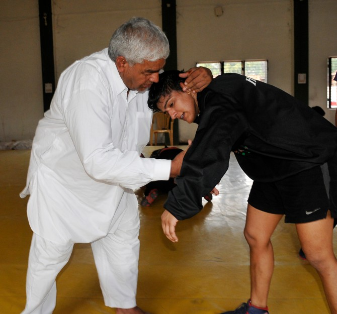 Mahavir wrestles with Ritu during a training session.