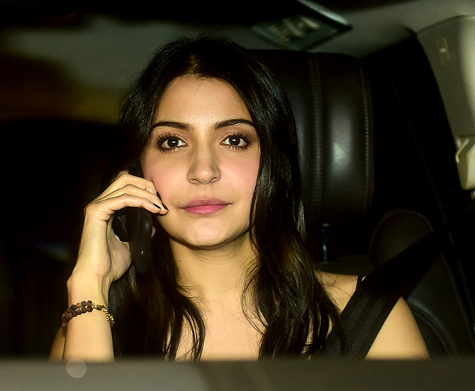 Anuska Sharma chats on her phone, seat belt firmly in place.