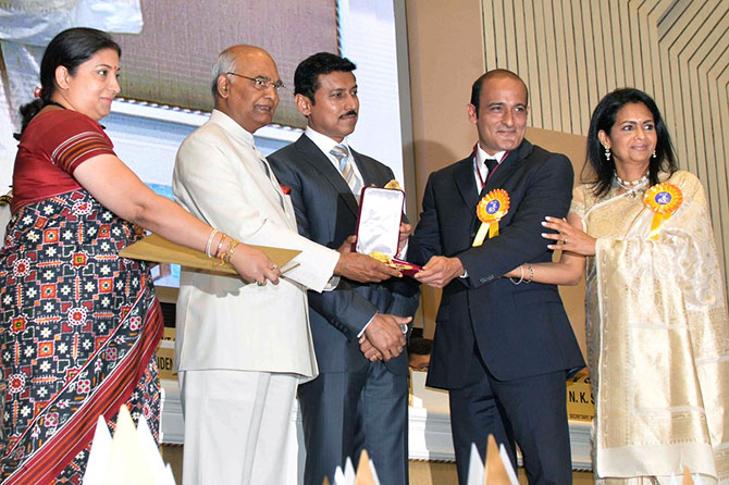President Ram Nath Kovind presents the Dadasaheb Phalke Award to Vinod Khanna's son Akshay Khanna and his wife Kavita Khanna as then information and broadcasting minister Smriti Irani, left, and her successor Colonel Rajyavardhan Singh Rathore (retd), third from left, look on.
