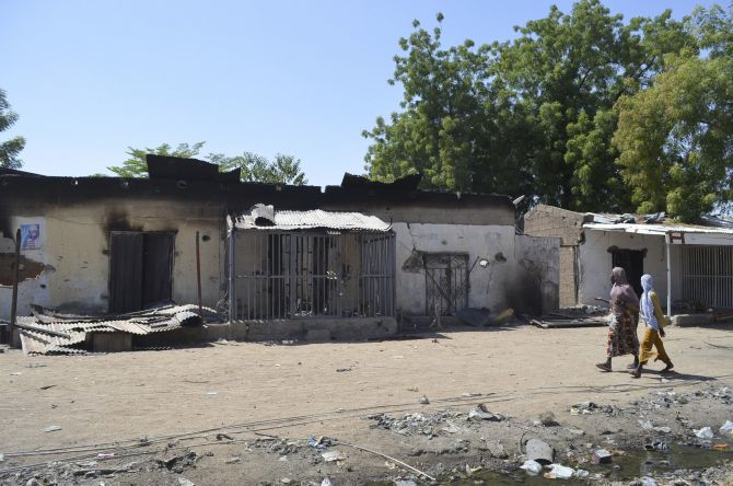 Women walk by homes destroyed by Boko Haram militants in Bama, Borno State