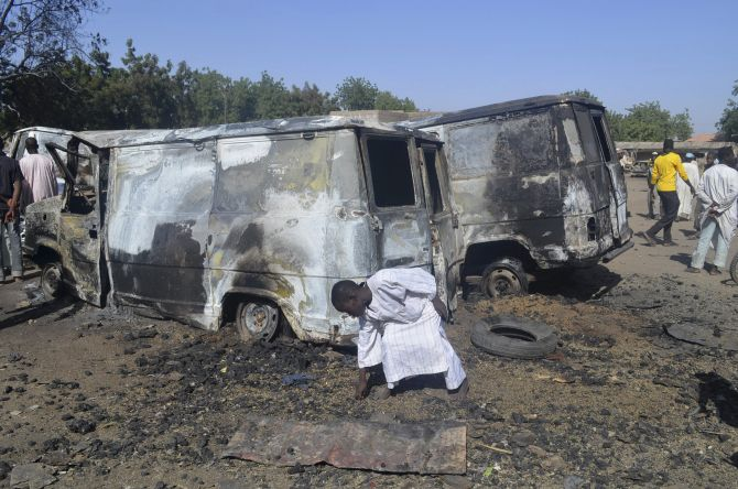 A boy searches the ground next to a burnt-out vehicle, caused by an attack from Boko Haram militants, in Bama, Borno