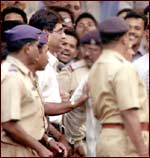 R S Sharma (bespectacled man wearing white shirt) being produced in a Pune court. Pic: Arun Patil