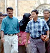 Patani (head covered) being led to the court. Photo: Arun Patil