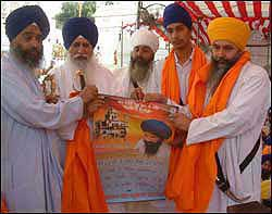 Bhai Manjit Singh, Amrik Singh's brother, and others holding a calendar depicting a shattered Akal Takht