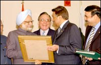 President Musharraf (R) offers a present to Prime Minister Manmohan Singh