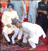 Bihar governer Buta Singh being helped by a man in removing his shoes in state function
