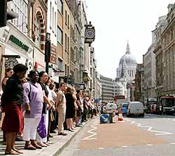 Office workers line the kerb in London's Fleet Street  July 14 during a two minute silence held across Britain in memory of the victims of last week's bomb atttacks In the  background is the dome of St.Paul's Cathedral.(AP Photo/Dimitri Messinis)
