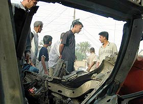 People check the aftermath of a car bomb explosion in Klais, some 45 km north of Baqouba, June 2. (AP PHOTO)