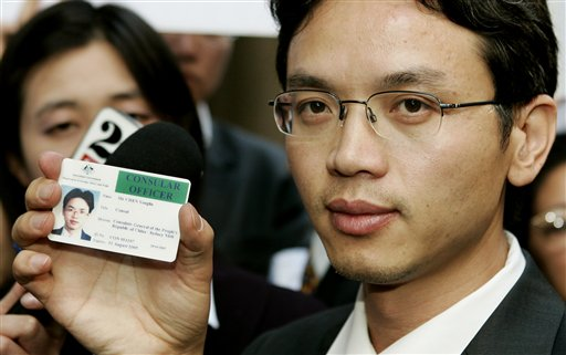 Chinese diplomat Chen Yonglin  holds up his Chinese consular identity card to the media at a rally to commemorate the June 4, 1989 crackdown on the Tiananmen Square pro-democracy protests in Beijing,  in Sydney, Australia, Saturday, June 4. Chen is seeking political asylum in Australia  (AP Photo/Mark Baker)