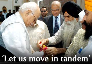 A Pakistani Sikh offers a garland to BJP chief LK Advani, on his arrival to visit a Sikh temple in Lahore, Pakistan on Friday, June 3, 2005. AP Photo/K M  Chaudhry