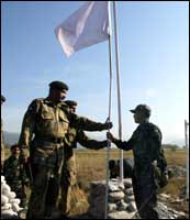A Pakistani army officer (C) hands over a white peace flag to an Indian army officer at the Line of Control on November 7, in an historic move to help earthquake-striken people from the region.