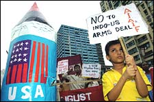 An schoolboy displays a placard hostile to a recent Indian-US nuclear deal next to a mock nuclear bomb during an anti-nuclear protest in Kolkata, August 6, 2005. Deshakalyan Chowdhury/AFP/Getty Images)