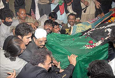 Asif Ali Zardari, husband of former Pakistan prime minister Benazir Bhutto, lowers her coffin into the grave