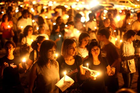 Mumbai residents walk with candles in the street near The Oberoi Hotel