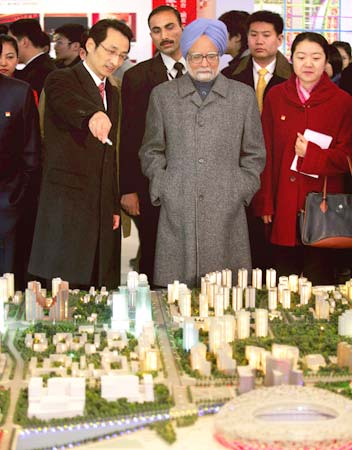 Prime Minister Manmohan Singh looks on as Beijing Vice-Mayor Chen Gang (Left) introduces a model of the Olympic Green in Beijing, China