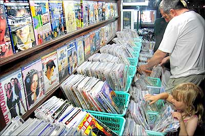 Tourists go through an assortment of pirated music CDs and DVDs