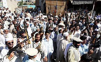 Pakistani men from tribal forces chant slogans against the Taliban in Raghagan