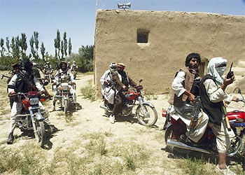 Taliban fighters ride on motorbikes in an undisclosed location in Afghanistan