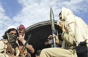 Pakistani Taliban fighters sit with their weapons on the back of a truck in Buner