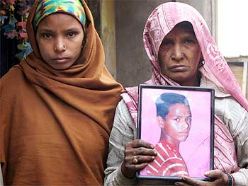 The blind mother and younger sister of 20-year-old Pradeep Singh hold a picture of him. He died after suffering severe beating by the police in Chitti, Dhankaur. They still have received no compensation