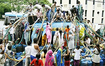 Residents of Sanjay Colony, a residential area, crowd around a water tanker in New Delhi.