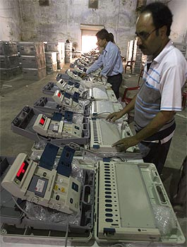 Technicians check EVMs at an election office