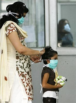 A mother puts on a surgical mask for her daughter as they arrive for a H1N1 flu screening at Ram Manohar Lohia hospital in New Delhi