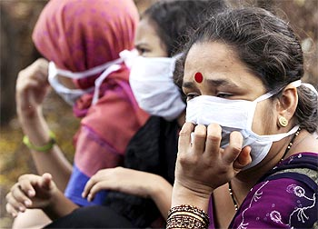 Women wearing masks wait to receive medical attention for suspected H1N1 influenza at a hospital in Pune