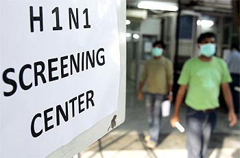 People wearing surgical masks walk out of a H1N1 flu screening centre in Ram Manohar Lohia hospital in New Delhi