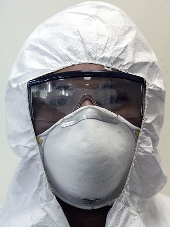 A hospital worker models a biohazard suit, safety goggles and a mask in San Salvador