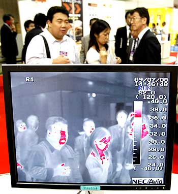 Visitors walk behind a NEC Avio Infrared Technologies Co's thermo graphic examination system for use in detecting the H1N1 virus at the Office Security Expo in Tokyo