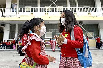 School girls wear protective masks as they stand outside their classrooms at an elementary school in Mexico City